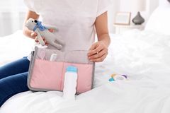 Woman packing baby accessories into maternity bag on bed. Closeup stock image