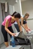 Woman packing bag at gym's locker room Royalty Free Stock Photo