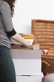 Woman packing books. A woman packing books into a cardboard box Stock Image