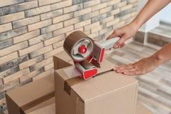 Woman packing carton box indoors, closeup. Moving day stock photos