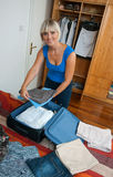 Woman packing clothes Royalty Free Stock Image