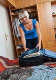 Woman packing clothes Stock Image