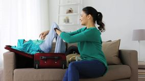 Woman packing clothes to travel bag at home. Tourism, people and luggage concept - happy young woman packing clothes to travel bag at home stock video