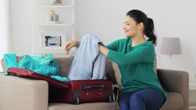 Woman packing clothes to travel bag at home. Tourism, people and luggage concept - happy young woman packing clothes to travel bag at home stock footage