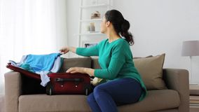 Woman packing clothes to travel bag at home. Tourism, people and luggage concept - happy young woman packing clothes to travel bag at home stock video footage
