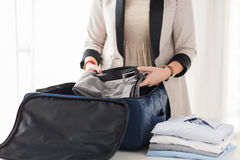 Woman packing formal male clothes into travel bag. Business, trip, luggage and people concept - close up of woman formal male clothes into travel bag at home Stock Photo