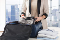 Woman packing formal male clothes into travel bag. Business, trip, luggage and people concept - close up of woman formal male clothes into travel bag at home or Royalty Free Stock Photos