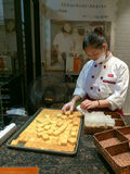 A woman packing freshly-baked pipeapple cake in a cake store in Xiamen city, China Royalty Free Stock Photos