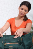 Woman packing green bag Stock Images