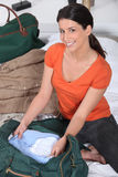 Woman packing her bag royalty free stock photos