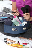 Woman packing her make-up bag Stock Images