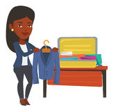 Woman packing her suitcase vector illustration. Stock Photography