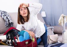 Woman packing for holiday. Smiling woman preparing to depart for holiday at home Royalty Free Stock Images