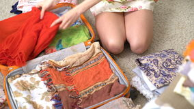 Woman packing a luggage for a new journey, red dress stock video footage