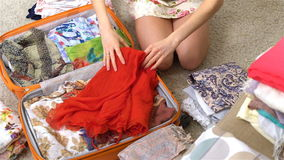 Woman packing a luggage for a new journey, red dress, slow motion stock footage