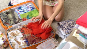 Woman packing a luggage for a new journey, red dress, slow motion stock video footage