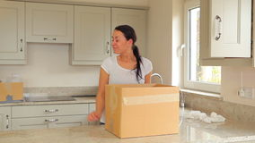 Woman packing moving box with man carrying boxes stock footage