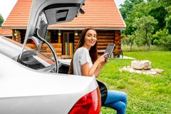 Woman packing near the car with house on Stock Photography