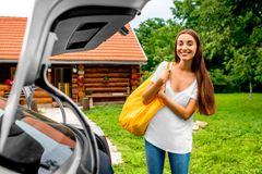 Woman packing near the car with house on Stock Photos
