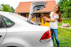 Woman packing near the car with house on Royalty Free Stock Photography
