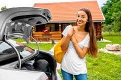 Woman packing near the car with house on Stock Images