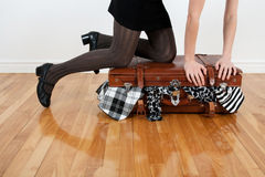 Woman packing overfilled suitcase Stock Photography