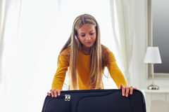 Woman packing suitcase on bed Stock Images