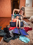 Woman packing suitcase with girl in flippers inside Royalty Free Stock Image