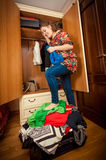 Woman packing suitcase on holiday at wardrobe Stock Image