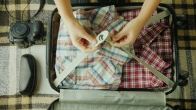A woman is packing a suitcase. It puts things together for travel. Go on vacation concept stock video footage