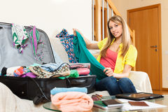 Woman packing a suitcase for travel. Happy young woman packing a suitcase for travel Royalty Free Stock Image