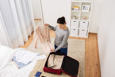 Woman packing travel bag at home or hotel room Royalty Free Stock Photo