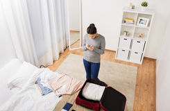 Woman packing travel bag at home or hotel room Stock Image