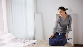 Woman packing travel bag at home or hotel room stock footage