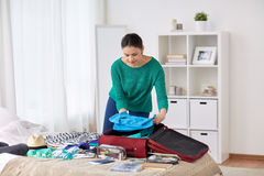 Woman packing travel bag at home or hotel room Stock Images