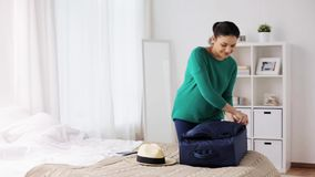 Woman packing travel bag at home or hotel room. Tourism, people and luggage concept - happy young woman packing travel bag at home or hotel room stock video footage