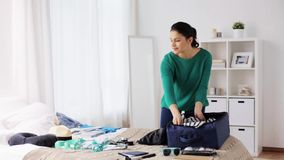 Woman packing travel bag at home or hotel room. Tourism, people and luggage concept - happy young woman packing travel bag at home or hotel room stock video