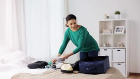 Woman packing travel bag at home or hotel room. Tourism, people and luggage concept - happy young woman packing travel bag at home or hotel room stock footage