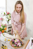 Woman packing tulip bouquet in flower shop. Young florist make festive floristry assemble in workshop on wooden background Stock Image