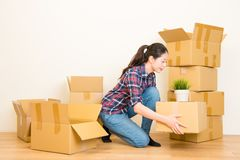 Woman packing and unpacking belongings. In a carton box when moving home. mixed race asian chinese model Royalty Free Stock Photos