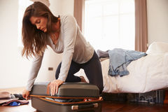Woman Packing For Vacation Trying To Close Full Suitcase Royalty Free Stock Photos