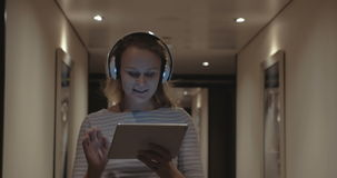 Woman with pad enjoying music in headphones stock video