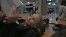 Woman with pad lying on the bench in airport terminal. Tired woman lying on the bench in airport lounge and using tablet computer while waiting for the flight stock video