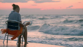 Woman with pad sitting on chair by rough sea stock footage