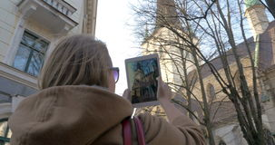 Woman with pad taking photo of historical building stock video
