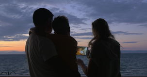 Woman with pad taking photo of husband with son. Young woman using tablet computer to make photo of son and father on the balcony with view to the evening sky stock video footage