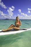 Woman on paddle board texting Stock Images