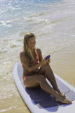 Woman on paddle board texting Royalty Free Stock Image
