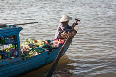 The woman with the paddle boat that carries to market fruits and vegetables from small  Royalty Free Stock Image