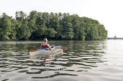 Woman in paddle boat. Young woman in paddle boat, rear view stock photography